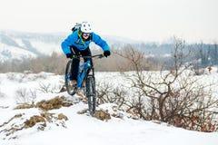 Ποδηλάτης στο μπλε οδηγώντας ποδήλατο βουνών στο δύσκολο χειμερινό Hill που καλύπτεται με το χιόνι Ακραίος αθλητισμός και έννοια  στοκ φωτογραφία
