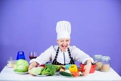 Ποδιά καπέλων ένδυσης αρχιμαγείρων γυναικών κοντά στα επιτραπέζια συστατικά Ο λατρευτός αρχιμάγειρας κοριτσιών διδάσκει μαγειρικό στοκ εικόνα