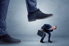 Ποδοπατημένος μικρός επιχειρηματίας στο κοστούμι Στοκ Εικόνες