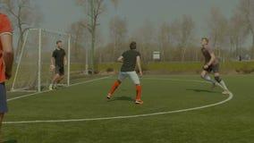 Ποδοσφαιριστής που ρίχνει τη σφαίρα μέσα επάνω στην πίσσα απόθεμα βίντεο