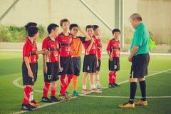 Ποδόσφαιρο παιδιών κατάρτισης προπονητών μετά από να παίξει στοκ εικόνα με δικαίωμα ελεύθερης χρήσης