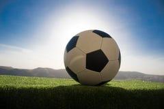 ποδόσφαιρο πεδίων σφαιρών Ποδόσφαιρο στην πράσινη χλόη ανασκόπηση ηλιόλουστη Στοκ φωτογραφία με δικαίωμα ελεύθερης χρήσης