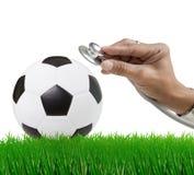 Ποδόσφαιρο ποδοσφαίρου στο πράσινο πεδίο χλόης με το χέρι και στοκ φωτογραφίες