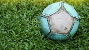 Ποδόσφαιρο στο χορτοτάπητα Παλαιά σφαίρα στην όμορφη πράσινη χλόη στον τομέα Στοκ Φωτογραφίες