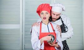 Ποια έκπληξη για τους Οικογενειακό μαγείρεμα στην κουζίνα μυστικό συστατικό από τη συνταγή μάγειρας ομοιόμορφος ζεύγος ερωτευμένο στοκ φωτογραφίες με δικαίωμα ελεύθερης χρήσης