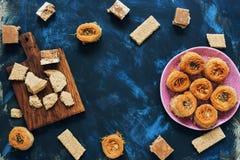 Ποικίλα ασιατικά γλυκά σε ένα μπλε υπόβαθρο Baklava, halva, sherbet, σουσάμι Τοπ άποψη, διάστημα αντιγράφων Στοκ φωτογραφία με δικαίωμα ελεύθερης χρήσης