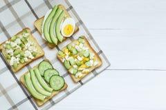 Ποικιλία των σάντουιτς για το πρόγευμα, πρόχειρο φαγητό, αβοκάντο, αυγό, τυρί κρέμας στα σάντουιτς ψωμιού, άσπρο υπόβαθρο στοκ εικόνες