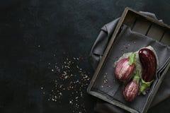 Ποικιλίες μελιτζάνας στο μαύρο κύπελλο πέρα από το σκοτεινό υπόβαθρο πλακών Στοκ Φωτογραφία