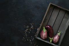 Ποικιλίες μελιτζάνας στο μαύρο κύπελλο πέρα από το σκοτεινό υπόβαθρο πλακών στοκ εικόνα