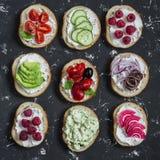 Ποικιλία των σάντουιτς - τα σάντουιτς με το τυρί, ντομάτες, αντσούγιες, έψησαν τα πιπέρια, σμέουρα, αβοκάντο, πατέ φασολιών, αγγο Στοκ Εικόνες