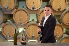 Ποιότητα επιθεώρησης Winemaker του κόκκινου κρασιού, που στέκεται κοντά στα ράφια μπουκαλιών στον υπόγειο θάλαμο οινοποιιών στοκ φωτογραφία