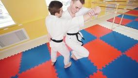 Πολεμικές τέχνες Δύο αθλητικά άτομα που εκπαιδεύουν τις δεξιότητες aikido τους Parries το χτύπημα και ρίψη του αντιπάλου στο πάτω φιλμ μικρού μήκους
