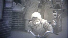 ΠΟΛΗ ΤΗΣ ΝΕΑΣ ΥΌΡΚΗΣ - 1946: Οδηγώντας ποδήλατο αγοριών στις οδούς μετά από ένα τοπικό αστικό περίπτερο εφημερίδων απόθεμα βίντεο