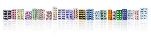 Πολλά από τα ζωηρόχρωμα χάπια στα πακέτα φουσκαλών σε μια σειρά στο άσπρο υπόβαθρο με το διάστημα αντιγράφων Βιομηχανία φαρμακευτ στοκ φωτογραφία