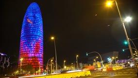 Πολλά αυτοκίνητα που ορμούν από φωτισμένο Torre Agbar, ταραχώδης ζωή πόλεων νύχτας, χρόνος-σφάλμα φιλμ μικρού μήκους