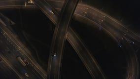 Πολλά αυτοκίνητα στην τεράστια οδική σύνδεση Νύχτα στην ανταλλαγή αυτοκινητόδρομων 4k κεραία απόθεμα βίντεο