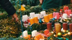 Πολλά διαφορετικά πολύχρωμα κεριά ως διακοσμήσεις για τα Χριστούγεννα και το νέο έτος περιβάλλονται από τους κλάδους του ελαιόπρι απόθεμα βίντεο
