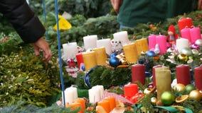 Πολλά διαφορετικά πολύχρωμα κεριά ως διακοσμήσεις για τα Χριστούγεννα και το νέο έτος περιβάλλονται από τους κλάδους του ελαιόπρι φιλμ μικρού μήκους