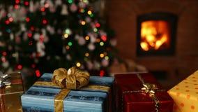 Πολλά δώρα Χριστουγέννων μπροστά από την εστία και μουτζουρωμένα φω'τα στο χριστουγεννιάτικο δέντρο φιλμ μικρού μήκους