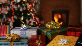 Πολλά δώρα Χριστουγέννων μπροστά από την εστία και μουτζουρωμένα φω'τα στο χριστουγεννιάτικο δέντρο απόθεμα βίντεο