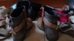 Πολλά ζευγάρια των παπουτσιών στέκονται σε μια σειρά φιλμ μικρού μήκους