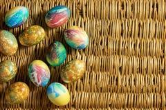 Πολλά ζωηρόχρωμα αυγά Πάσχας είναι στο υπόβαθρο των πλεγμένων κλάδων ιτιών Στοκ Φωτογραφίες