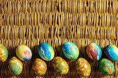 Πολλά ζωηρόχρωμα αυγά Πάσχας είναι στο υπόβαθρο των πλεγμένων κλάδων ιτιών Στοκ Φωτογραφία