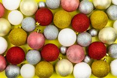 Πολλά ζωηρόχρωμα μπιχλιμπίδια Χριστουγέννων βρίσκονται σε ένα κίτρινο υπόβαθρο, διακοσμήσεις Χριστουγέννων στοκ φωτογραφία