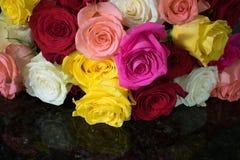 Πολλά ζωηρόχρωμα τριαντάφυλλα τακτοποίησαν πάνω από το μαύρο γρανίτη στοκ εικόνες