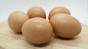 Πολλά καφετιά αυγά κοτόπουλου στον τεμαχίζοντας πίνακα με το άσπρο υπόβαθρο Στοκ Φωτογραφίες