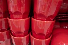Πολλά κόκκινα φλυτζάνια είναι στο ράφι στοκ εικόνες