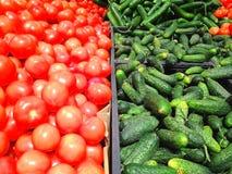 Πολλά κόκκινες ντομάτες και πράσινα αγγούρια που βρίσκονται στην υπεραγορά Στοκ Εικόνες