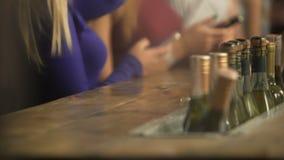Πολλά μπουκάλια του κρασιού στην αντίθετη, ενεργό ατμόσφαιρα φραγμών στο μπαρ, γυναίκες με τα τηλέφωνα απόθεμα βίντεο