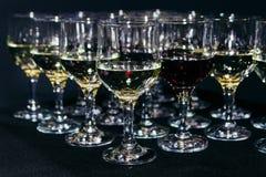 Πολλά ποτήρια του διαφορετικού κρασιού στο μαύρο μετρητή φραγμών Στοκ Εικόνες