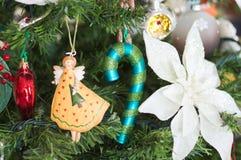 Πολλά πράγματα κρεμούν στο χριστουγεννιάτικο δέντρο: Άγιος Βασίλης, κουδούνια και σφαίρες, άτομο μελοψωμάτων και κάλαμοι καραμελώ Στοκ Εικόνες