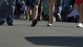 Πολλά πόδια ανθρώπων που περπατούν κατά μήκος της ευρείας αστικής οδού, φεστιβάλ πόλεων, σε αργή κίνηση φιλμ μικρού μήκους