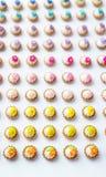Πολλά τεχνητά cupcakes στην άσπρη επιφάνεια με το ρηχό βάθος του υποβάθρου τομέων Στοκ Φωτογραφίες