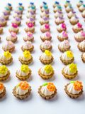 Πολλά τεχνητά cupcakes στην άσπρη επιφάνεια με το ρηχό βάθος του υποβάθρου τομέων Στοκ εικόνα με δικαίωμα ελεύθερης χρήσης