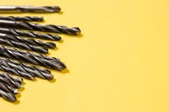 Πολλά τρυπάνια σε έναν χλωμό - κίτρινο υπόβαθρο Στοκ φωτογραφία με δικαίωμα ελεύθερης χρήσης