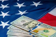 πολλά χρήματα 100 δολάρια στο υπόβαθρο της αμερικανικής σημαίας στοκ φωτογραφία