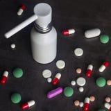 Πολλά χρωματισμένα χάπια και άσπρο inhaler σε ένα σκοτεινό υπόβαθρο Phar Στοκ Φωτογραφίες