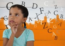 Πολλές επιστολές γύρω από τη σκέψη κοριτσιών μπροστά από χρωματισμένο το πορτοκάλι υπόβαθρο Στοκ φωτογραφία με δικαίωμα ελεύθερης χρήσης