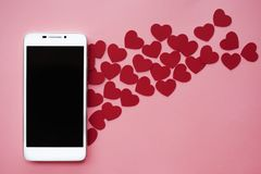 Πολλές καρδιές και smartphone Έννοια σε ομοειδή στα κοινωνικά δίκτυα ή τη χρονολόγηση app Ρόδινη ανασκόπηση Στοκ φωτογραφία με δικαίωμα ελεύθερης χρήσης