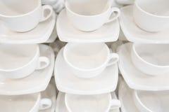 Πολλές σειρές καθαρίζουν το άσπρο φλυτζάνι καφέ, το κουτάλι τσαγιού και το πιατάκι στον πίνακα Η κενή κούπα που τίθεται στη σειρά Στοκ Εικόνα
