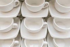 Πολλές σειρές καθαρίζουν το άσπρο φλυτζάνι καφέ, το κουτάλι τσαγιού και το πιατάκι στον πίνακα Η κενή κούπα που τίθεται στη σειρά Στοκ Φωτογραφία