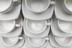 Πολλές σειρές καθαρίζουν το άσπρο φλυτζάνι καφέ, το κουτάλι τσαγιού και το πιατάκι στον πίνακα Η κενή κούπα που τίθεται στη σειρά Στοκ εικόνες με δικαίωμα ελεύθερης χρήσης