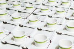 Πολλές σειρές του άσπρου φλυτζανιού κενές και των δίσκων με το κουταλάκι του γλυκού που τοποθετείται υπέροχα στον πίνακα στοκ φωτογραφίες