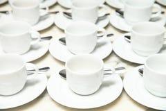 Πολλές σειρές του άσπρων κεραμικών φλυτζανιού και του πιατακιού με το κουταλάκι του γλυκού Στοκ φωτογραφία με δικαίωμα ελεύθερης χρήσης