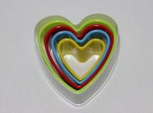 Πολλή καρδιά που διαμορφώνεται της πλαστικής φόρμας επιδορπίων στο πολυ χρώμα που απομονώνεται στο άσπρο υπόβαθρο Στοκ Εικόνα