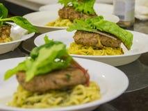 Πολλή μπριζόλα του Αμβούργο εξυπηρετεί με το νουντλς και το λαχανικό στοκ φωτογραφία με δικαίωμα ελεύθερης χρήσης